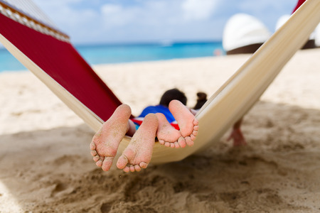 Brother and sister kids relaxing in hammock at tropical beach 스톡 콘텐츠