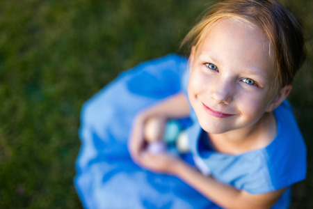 child portrait: Above view of adorable little girl playing with colorful Easter eggs outdoors on a grass at spring