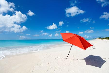 赤い傘、白い砂浜、ターコイズ ブルーの海の水とカリブ海の無人島で青い空のどかな熱帯のビーチ