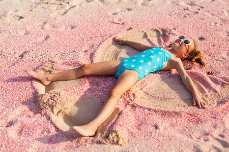 Liten flicka gör sand ängel på vackra rosa sandstrand vid tropiska ön Barbuda i Västindien Stockfoto
