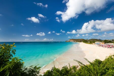 antigua: Idyllic tropical Darkwood beach at Antigua island in Caribbean with white sand, turquoise ocean water and blue sky