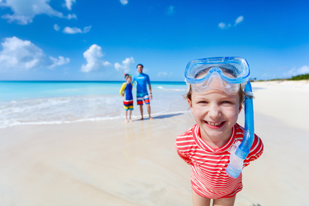 Little girl and her family with snorkeling equipment enjoying beach vacation