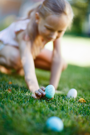 easter egg hunt: Adorable little girl on Easter eggs hunt collecting colorful eggs outdoors on a grass at spring Stock Photo