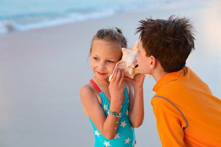 swimwear: Two kids with giant shell at beach listening to the sea Stock Photo