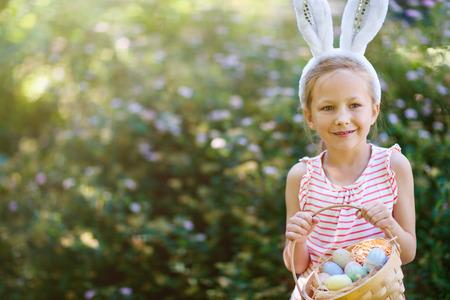 huevos de pascua: Niña adorable con orejas de conejo sosteniendo una canasta con huevos de Pascua al aire libre en día de primavera Foto de archivo
