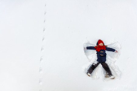 Above view of adorable little girl enjoying beautiful winter day making snow angel 스톡 콘텐츠