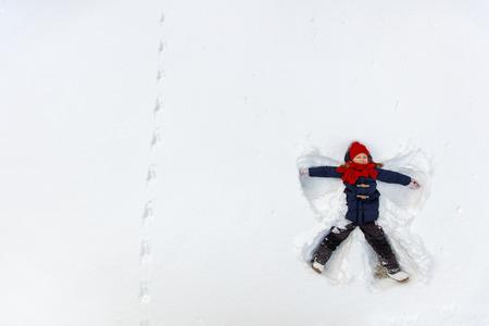 Above view of adorable little girl enjoying beautiful winter day making snow angel Foto de archivo