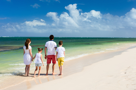 beach view: Back view of beautiful family at beach during summer vacation Stock Photo