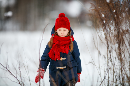 warm clothing: Adorable little girl wearing warm clothes outdoors on beautiful winter snow day Stock Photo