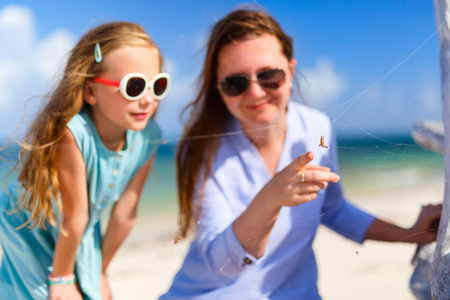 spider net: Beautiful mother and her adorable little daughter on beach looking together at spider net