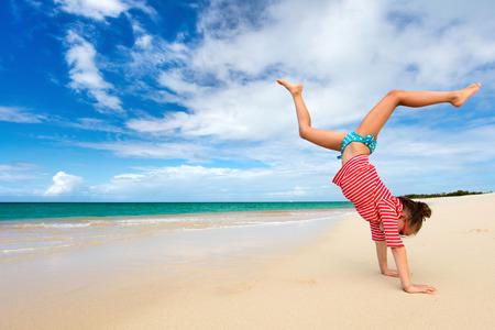 acrobacia: Niña adorable en la playa durante las vacaciones de verano