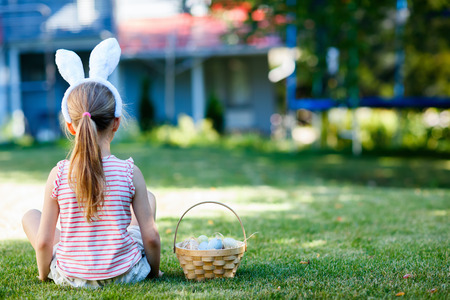 back view: Back view of a  little girl wearing bunny ears with a basket of colorful Easter eggs outdoors on spring day Stock Photo