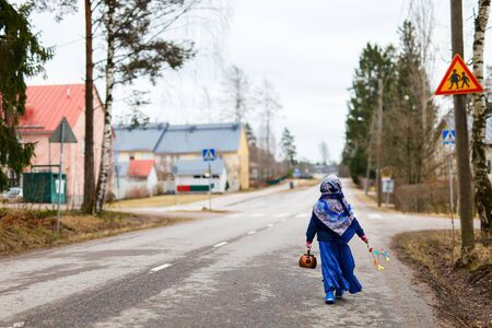 Back view of adorable little girl outdoors dressed for Easter traditional celebration in Finland