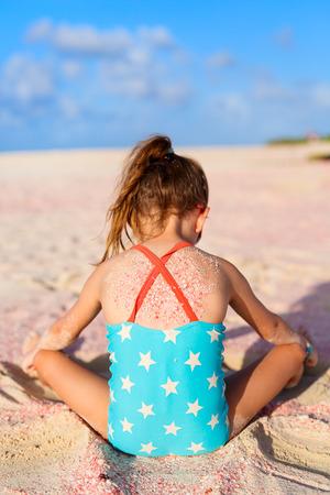 traje de baño: Niña adorable en la playa de arena de color rosa durante las vacaciones de verano