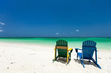 azul turqueza: Coloridos sillones verdes y azules en la playa tropical en el Caribe con hermosa agua de mar azul turquesa, arena blanca y azul cielo
