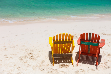 chairs: Colorful adirondack yellow and orange lounge chairs at tropical beach in Caribbean with beautiful turquoise ocean water, white sand and blue sky