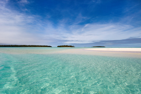south pacific: Stunning tropical lagoon and exotic islands with palm trees, white sand, turquoise ocean water and blue sky at Cook Islands, South Pacific