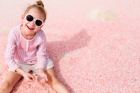 small girl: Adorable little girl playing with sand and shells on unique pink sand beach on Barbuda tropical island in Caribbean Stock Photo