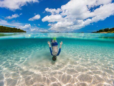 half: Split of above and underwater photo of cute little boy swimming in ocean