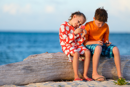 Kids playing on a portable game device or smartphone at beach Stock Photo