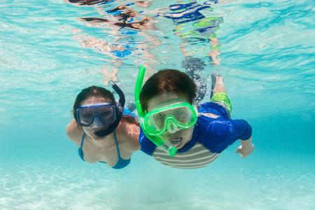 underwater ocean: Underwater photo of mother and son family snorkeling in turquoise ocean water
