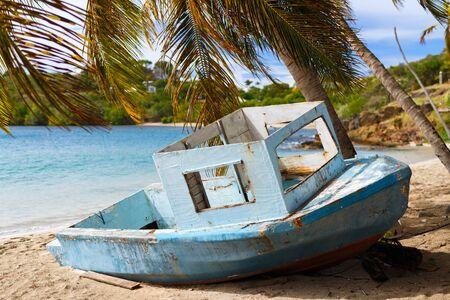 turquesa: barco de madera vieja en la playa tropical con palmeras, arena blanca, agua turquesa del océano y cielo azul en la isla de Antigua en el Caribe