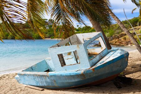 turquoise water: Old wooden boat at tropical beach with palm trees, white sand, turquoise ocean water and blue sky at Antigua Island in Caribbean