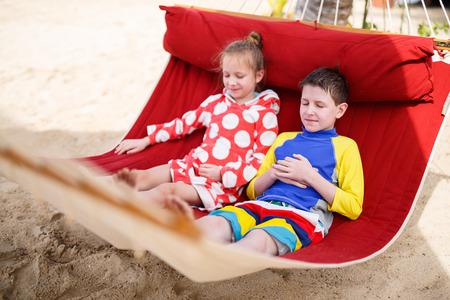Hermano y hermana cabritos que se relajan en hamaca en la playa tropical