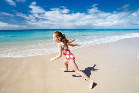 gente saltando: Ni�a feliz corriendo y chapoteando en el agua baja en la playa de tener un mont�n de diversi�n en las vacaciones de verano