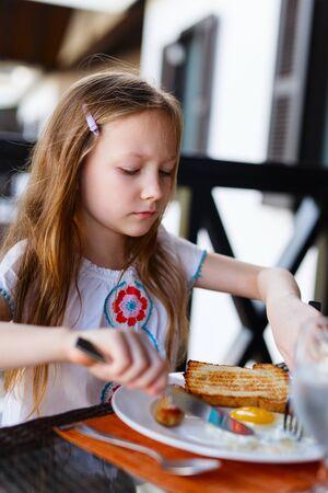 niña comiendo: Niña adorable que come el desayuno en el restaurante