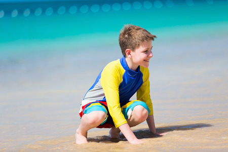 pre adolescent boy: Handsome pre-teen age boy playing with sand at tropical beach on summer vacation