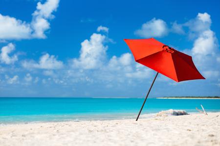 Rode paraplu op idyllisch tropisch strand met wit zand, turquoise oceaanwater en blauwe hemel bij verlaten eiland in het Caribisch gebied