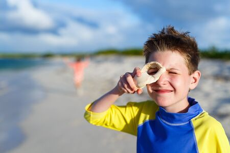 pre teen boy: Happy boy with shell at tropical beach during summer vacation