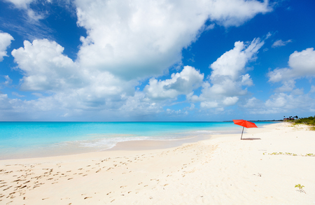 antigua: Red umbrella on Idyllic tropical beach with white sand, turquoise ocean water and blue sky at deserted island in Caribbean