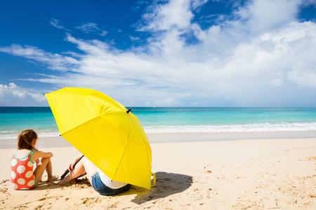sun umbrella: Mother and daughter with big yellow umbrella hiding from sun at tropical beach Stock Photo