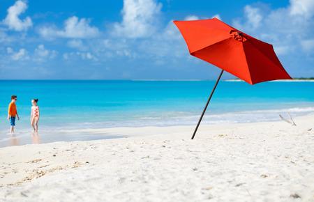 playas tropicales: Paraguas rojo en la playa tropical idílica con arena blanca, agua turquesa del océano y el cielo azul en la isla desierta en el Caribe