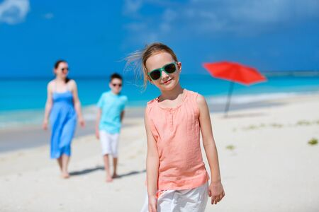 family vacation: Adorable little girl and her family on a tropical beach vacation Stock Photo