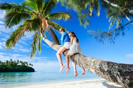 south pacific: Mother and little girl at tropical beach sitting on palm tree during summer vacation on exotic island in South Pacific Stock Photo