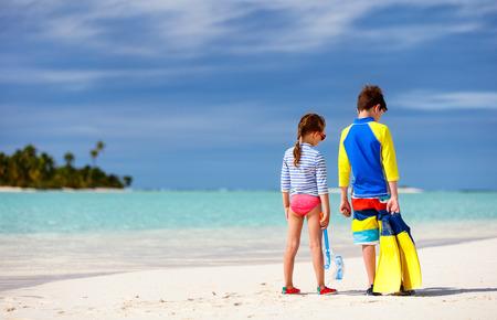 Kleine Kinder in Ausschlag Wachen für den Sonnenschutz mit Schnorchelausrüstung am tropischen Strand während der Sommerferien