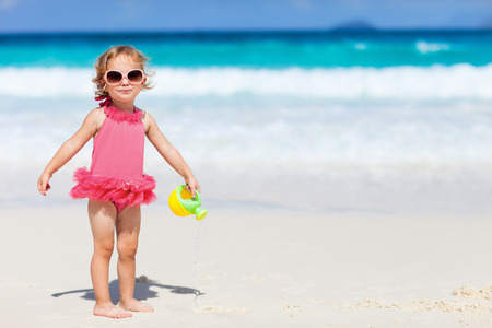 swimsuite: Adorable toddler girl in pink swimsuite playing with beach toys on white sand tropical beach Stock Photo