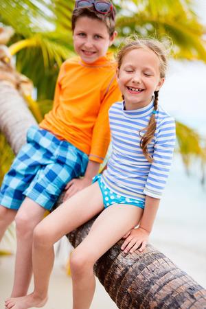 traje de baño: hermano y hermana niños disfrutan de tiempo en la playa tropical que se sienta en Palma que se cierne