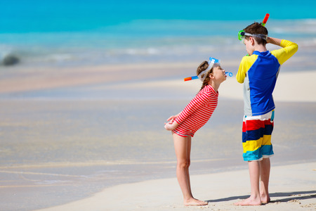 sun protection: Little kids in rash guards for sun protection with snorkeling equipment on tropical beach having fun during summer vacation