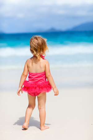 white playful: Back view of playful toddler girl on white sand tropical beach Stock Photo