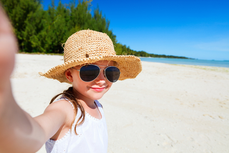 sun glasses: Adorable little girl making selfie in at tropical beach on exotic island during summer vacation