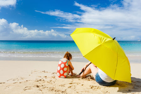 yellow umbrella: Mother and daughter with big yellow umbrella hiding from sun at tropical beach Stock Photo
