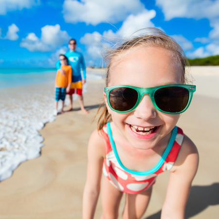 Little girl and her family father and brother enjoying beach vacation on Caribbean photo