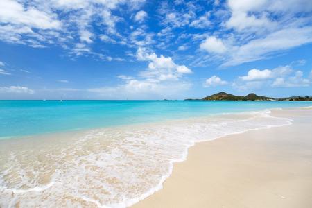 Idyllischer tropischer Strand mit weißem Sand, türkisfarbene Meer Wasser und blauer Himmel auf Antigua Insel in Karibik
