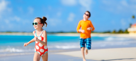 beach panorama: Kids having fun at tropical beach during Caribbean summer vacation playing together at shallow water