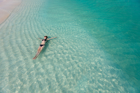 woman floating: Beautiful woman floating in turquoise tropical water Stock Photo