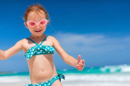 traje de baño: Feliz niña que disfruta de vacaciones de vacaciones en la playa